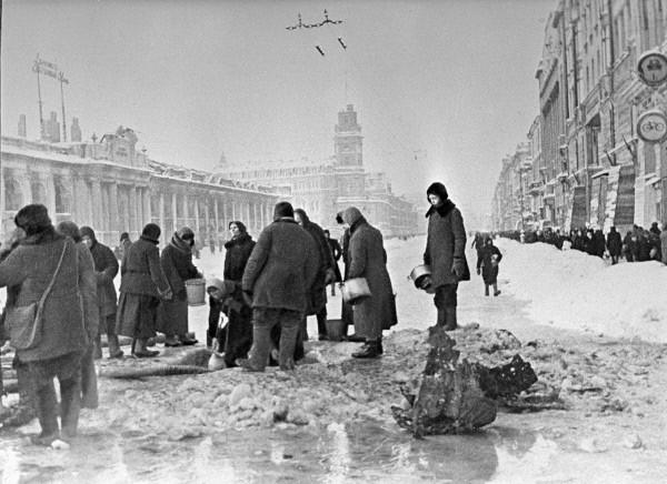 Жители блокадного Ленинграда набирают воду, появившуюся после артобстрела в пробоинах в асфальте на Невском проспекте. Фото Б. П. Кудоярова. декабрь 1941